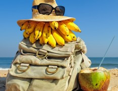 Knapsack, hat and fruit on the sandy beach